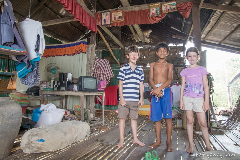 western kids with their cambodian friend in the floating village of Kamphong Phluk